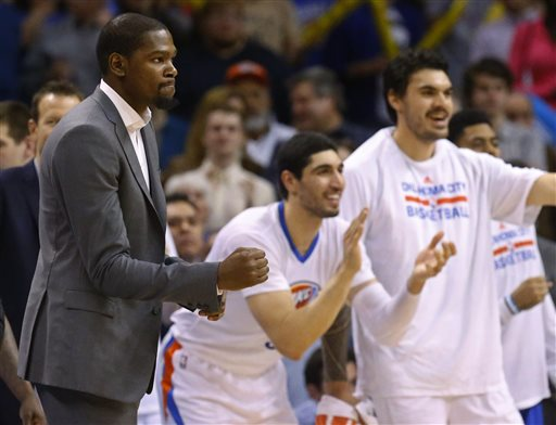 FILE - In this March 8, 2015, file photo, injured Oklahoma City Thunder forward Kevin Durant, left, pumps his fist as teammates Enes Kanter, center, and Steven Adams, right, cheer during the fourth quarter of an NBA basketball game against the Toronto Raptors in Oklahoma City. Durant will have bone graft surgery next week to deal with a fractured bone in his right foot, and he will miss the rest of the season, the Oklahoma City Thunder announced Friday, March 27, 2015.  (AP Photo/Sue Ogrocki, File)